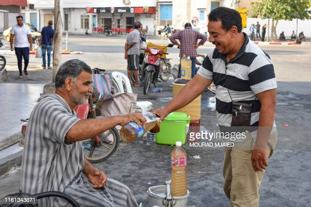 A customer buys a glass of legmi from a street vendor a coveted date palm drink in the southwestern Tunisian town of Gabes on July 18 2019 In...