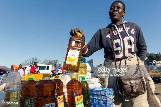 Customer buys cooking oil at a stall where smaller than standard measures of cooking oil is sold at Harare Mbare Musika marketplace on July 15, 2019....