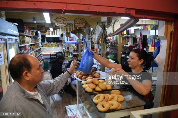 A customer buys food at a latin America's style bakery at the Seven Sisters indoors market in north London on June 15 2019 Looming redevelopment...
