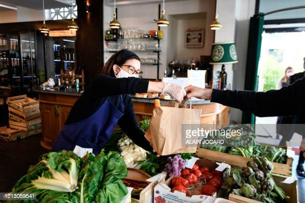 Customer buys food for take away at the L'Oseille restaurant where people can also buy fresh fruits and vegetables, on May 15, 2020 in Paris, a few...