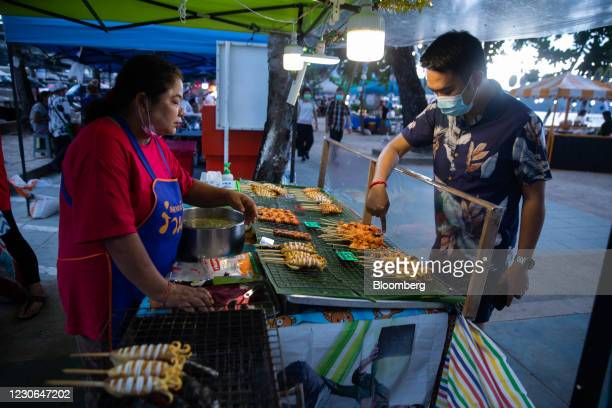 Customer buys grilled seafood from a stall at a market in Patong, Phuket, Thailand, on Saturday, Dec. 19, 2020. The tepid response to Thailands...