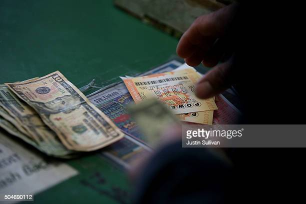 A customer buys Powerball tickets at Kavanagh Liquors on January 12 2015 in San Lorenzo California Dozens of people lined up outside of Kavanagh...