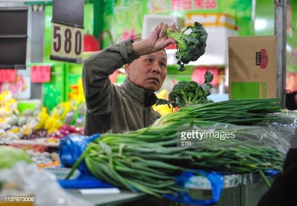 A customer buys vegetables at a market in Shenyang in China's northeastern Liaoning province on April 17 2019 China's economy beat forecasts as it...