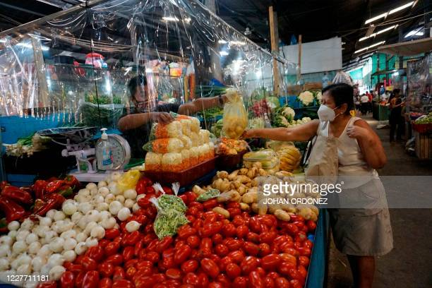Customer buys vegetables at a stall displaying a plastic curtain as a precaution against the spread of the new coronavirus, at La Asuncion market in...