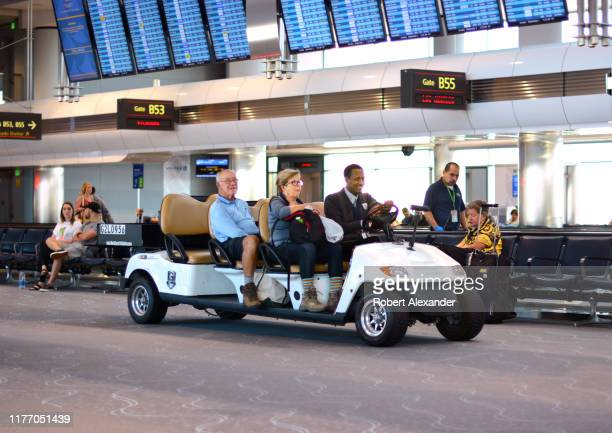 A customer care agent employed by G2 Secure transports passengers in a motorized airport passenger cart at Denver International Airport in Denver...