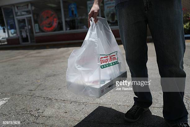 A customer carries a bag with Krispy Kreme donuts as he leaves the store on May 09 2016 in Miami Florida JAB Holdings Company announced it is...