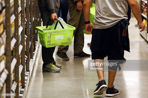 A customer carries a basket while shopping on the opening day of the 365 by Whole Foods Market store in the Silver Lake neighborhood of Los Angeles...