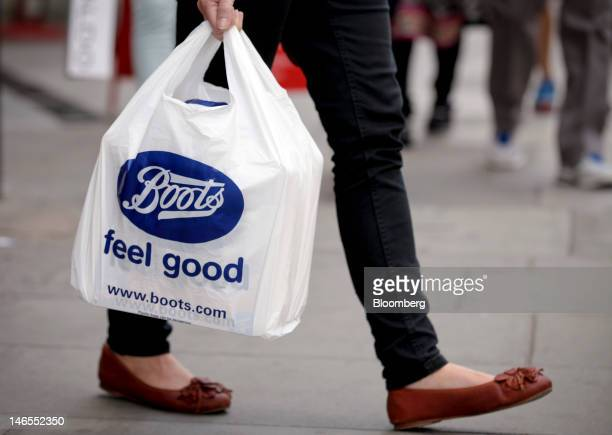 A customer carries a Bootsbranded carrier bag as she leaves one of the company's stores operated by Alliance Boots in London UK on Tuesday June 19...