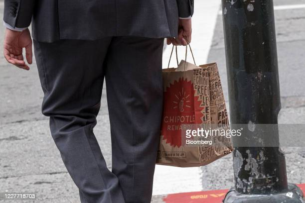 A customer carries a Chipotle Mexican Grill Inc bag outside a restaurant in San Francisco California US on Monday July 20 2020 Chipotle is scheduled...
