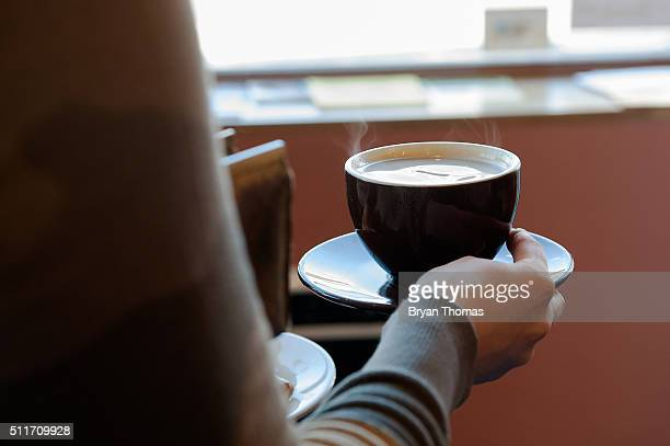 A customer carries a cup of coffee to her table at Colson Patisserie on February 22 2016 in the Brooklyn borough of New York City A recently released...