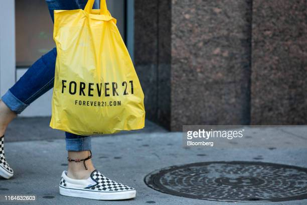 Customer carries a Forever 21 Inc. Shopping bag near a store in the Union Square neighborhood of New York, U.S., on Thursday, Aug. 29, 2019. Forever...