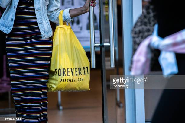 Customer carries a Forever 21 Inc. Shopping bag while exiting a store in the Union Square neighborhood of New York, U.S., on Thursday, Aug. 29, 2019....