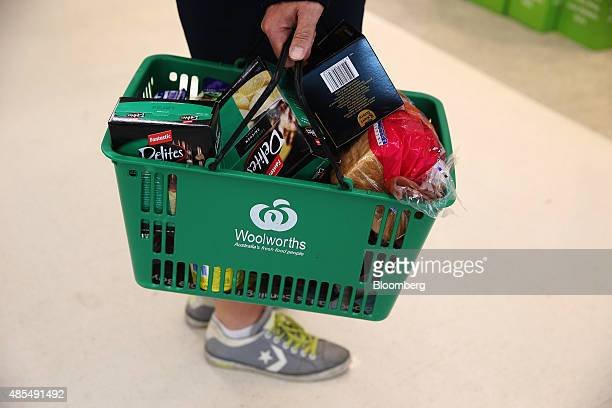 A customer carries a laden shopping basket at a Woolworths Ltd supermarket in Sydney Australia on Thursday Aug 27 2015 Woolworths Australias largest...