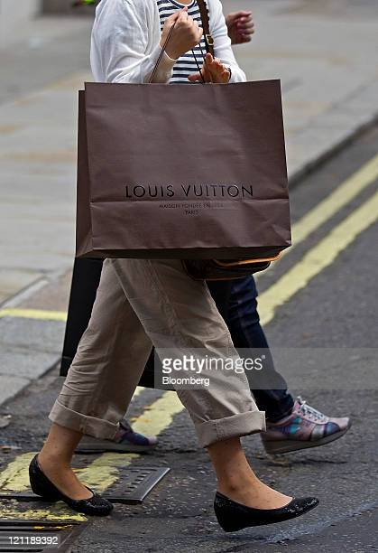 Customer carries a LVMH Moet Hennessy Louis Vuitton SA branded shopping bag on Old Bond Street in central London, U.K., on Monday, Aug. 15, 2011....