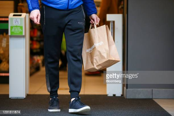 Customer carries a paper bag after shopping at the Amazon.com Inc. Amazon Fresh cashierless convenience store in the Ealing area of London, U.K., on...