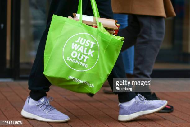 Customer carries a reusable bag after shopping at the Amazon.com Inc. Amazon Fresh cashierless convenience store in the Ealing area of London, U.K.,...