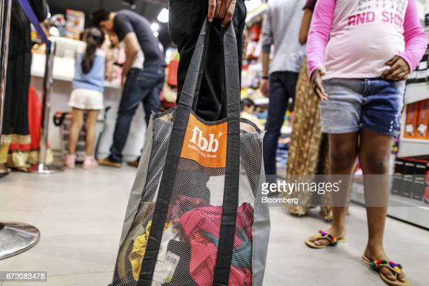 A customer carries a shopping bag bearing a logo for Fashion @ Big Bazaar the fashion unit of Big Bazaar operated by Future Retail Ltd at a Big...