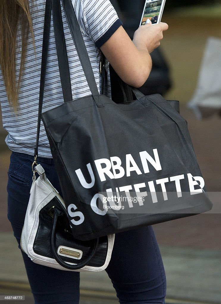A customer carries a shopping bag from an Urban Outfitters Inc ...