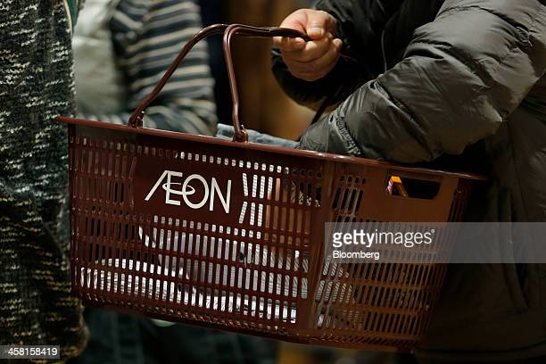 A customer carries a shopping basket bearing the Aeon Co logo at the Aeon Style Store in the Aeon Mall Makuhari Shintoshin shopping mall operated by...