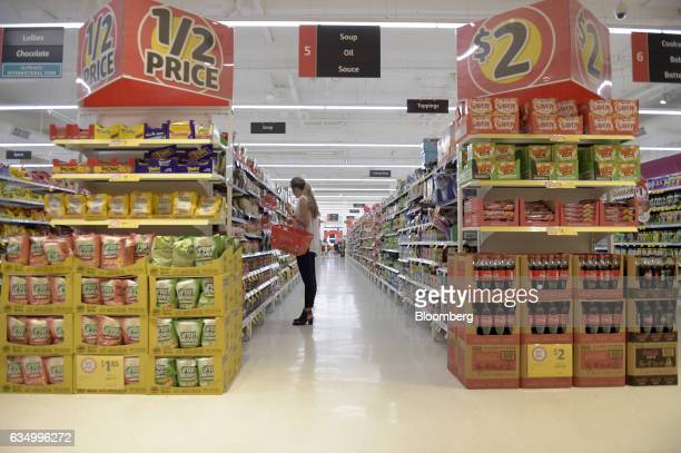 A customer carries a shopping basket while browsing through items in an aisle at a Coles supermarket operated by Wesfarmers Ltd in the Richmond area...