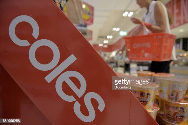 A customer carries a shopping basket while choosing groceries at a Coles supermarket operated by Wesfarmers Ltd in the Richmond area of Melbourne...