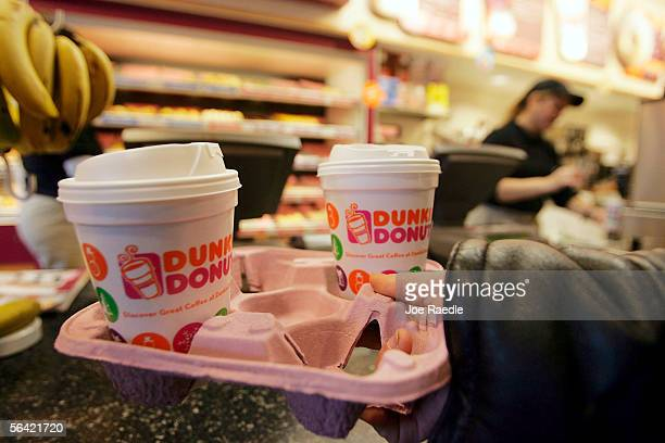 A customer carries a tray of coffee in a Dunkin' Donuts store December 12 2005 in Cambridge Massachusetts According to reports a group of private...