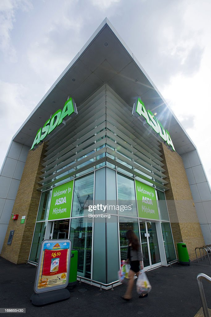 A customer carries her purchases in shopping bags as she leaves an Asda supermarket store, operated by Wal-Mart Stores Inc., in the Merton borough of London, U.K., on Monday, May 13, 2013. Asda, the U.K. supermarket chain owned by Wal-Mart Stores Inc., said sales rose 4.5 percent last year and it's investing 700 million pounds ($1 billion) into stores and online operations. Photographer: Jason Alden/Bloomberg via Getty Images