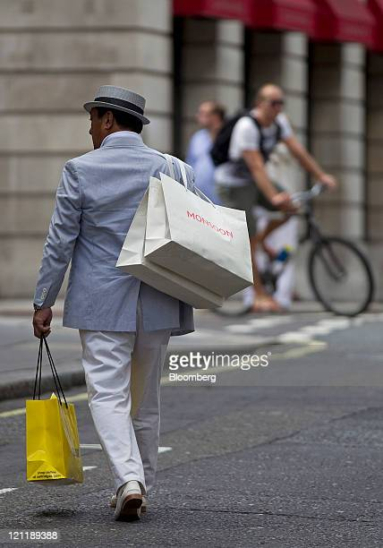 Customer carries Monsoon shopping bags across Old Bond Street in central London, U.K., on Monday, Aug. 15, 2011. U.K. Inflation probably accelerated...