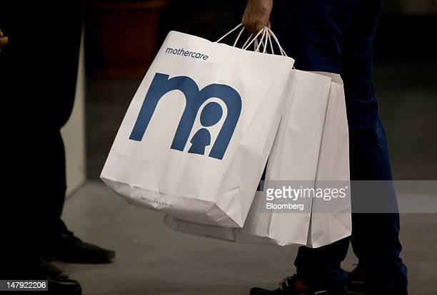 A customer carries Mothercare branded shopping bags in New Delhi India on Thursday July 5 2012 DLF Ltd India's largest realestate developer based in...