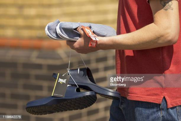A customer carries pairs of shoes purchased from a Sports Direct International Plc store in Crayford UK on Monday July 29 2019 Sports Direct plunged...