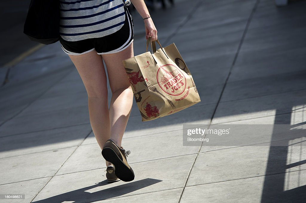 A customer carries shopping bags a Trader Joe's Co. shopping bag in San Francisco, California, U.S., on Friday, Sept. 13, 2013. Trader Joe's Co., the closely held grocery store chain, will end health benefits for part-time workers next year, directing them instead to anew insurance marketplaces as companies revamp medical coverage to fit the U.S. Affordable Care Act. Photographer: David Paul Morris/Bloomberg via Getty Images