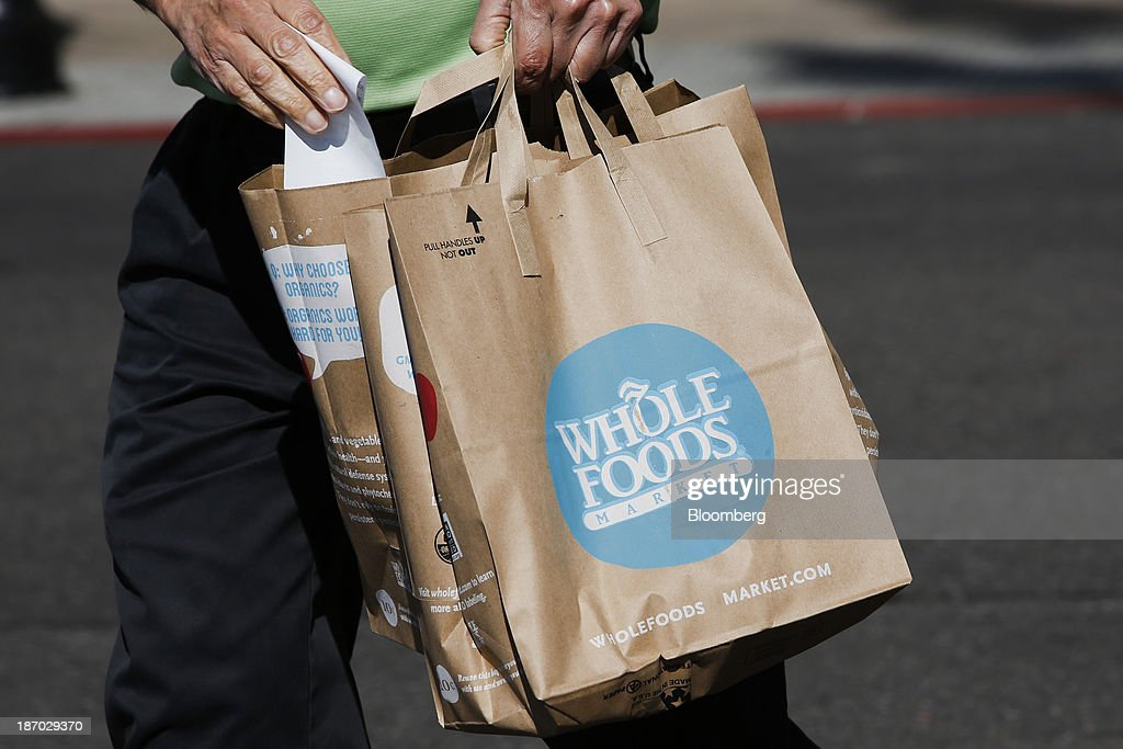 A customer carries shopping bags outside of a Whole Foods Market Inc. location in El Segundo, California, U.S., on Tuesday, Nov. 5, 2013. Whole Foods Market Inc. is scheduled to release earnings figures on Nov. 6. Photographer: Patrick T. Fallon/Bloomberg via Getty Images