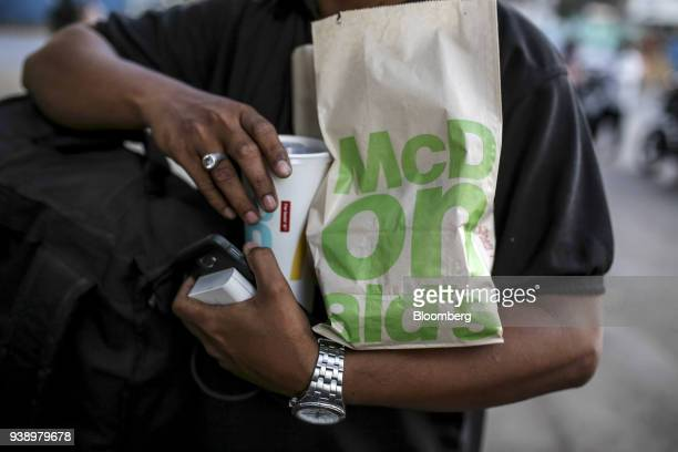 A customer carries takeout food from a McDonald's Corp restaurant operated by Hardcastle Restaurants Pvt in Mumbai India on Tuesday March 20 2018 As...