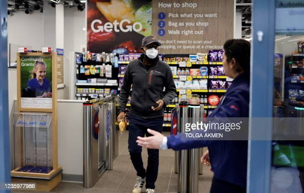 Customer carries the purchases as they leave from supermarket chain Tesco's first check-out free food store in Holborn, central London, on October...