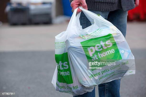 A customer carries their purchases in branded plastic carrier bags as they leave a Pets at Home Ltd store in London UK on Monday March 10 2014 Pets...