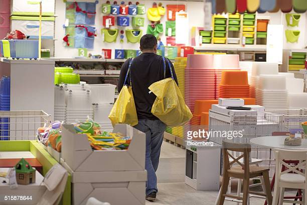 A customer carries two yellow Ikea inhouse shopping bags as he walks through the children's product section inside an Ikea AB store in Poznan Poland...