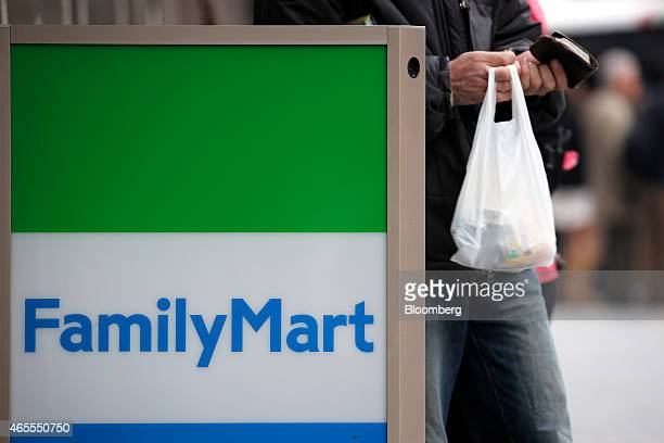 A customer carrying a shopping bag walks past a FamilyMart Co logo outside one of the company's convenience stores in Tokyo Japan on Saturday March 7...