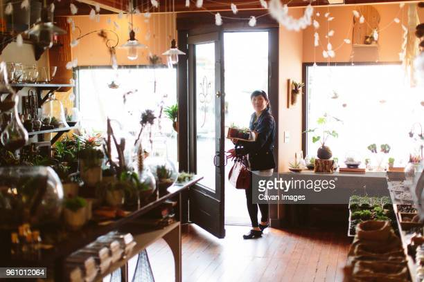 customer carrying crate of plants entering into garden center - entering stock pictures, royalty-free photos & images