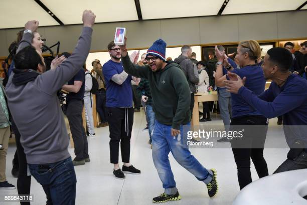 A customer center holds up an Apple Inc iPhone X after being the first to purchase the smartphone during the sales launch at a store in San Francisco...
