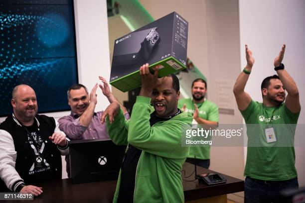 A customer center holds up an Xbox One X game console after being the first one to purchase the console during the Microsoft Corp global launch event...