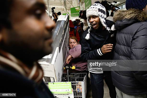 A customer center transports a boxed LED television in the basket of a mobility scooter during a Black Friday discount sale at an Asda supermarket...