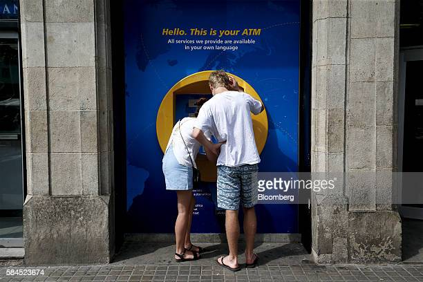 A customer checks a document while using an automated teller machine outside a CaixaBank SA bank branch in Barcelona Spain on Friday July 29 2016...
