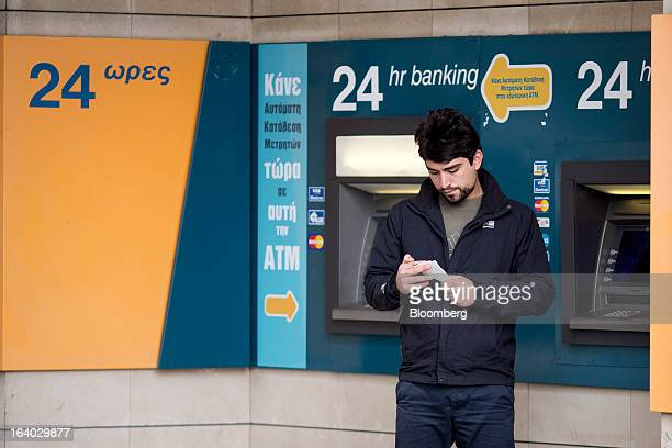 A customer checks his balance receipt at an automated teller machine operated by Bank of Cyprus Plc in Nicosia Cyprus on Tuesday March 19 2013...