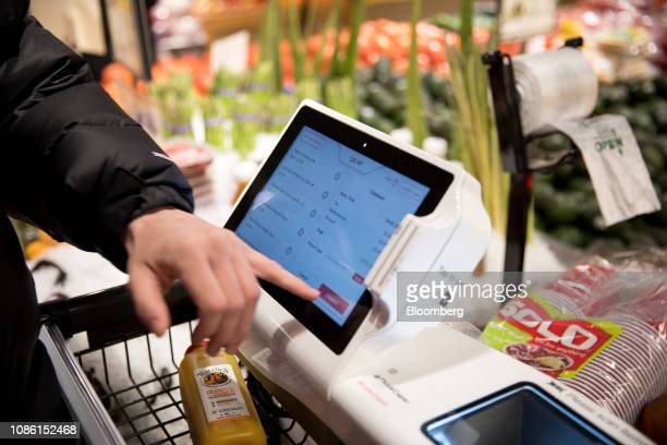 A customer checks out using a Caper Inc smart shopping cart at a Foodcellar Co grocery store in the Long Island City neighborhood in the Queens...