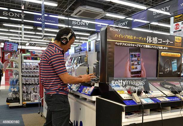 A customer checks products of Japanese electronics giant Sony at a shop in Tokyo on September 18 2014 Sony shares plunged 12 percent at the open in...