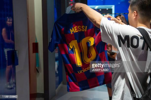 Customer cheecks out a new Barcelona FC home kit jersey bearing the name Barcelona's Argentinian forward Lionel Messi at the Spanish club's official...