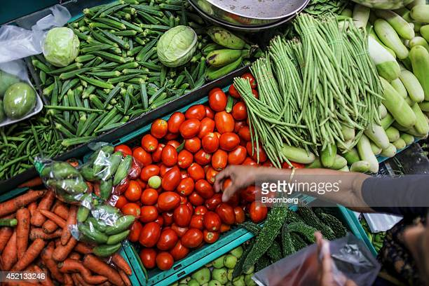 A customer chooses tomatoes at a fruitandvegetable market in Mumbai India on Sunday July 13 2014 Prime Minister Narendra Modis administration...