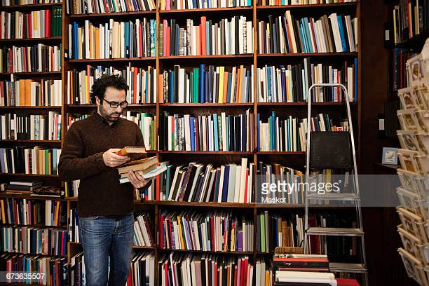 customer choosing book while standing against bookshelves - book store stock photos and pictures