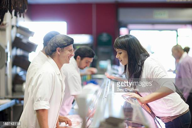 Customer choosing from butcher's counter