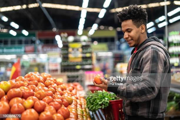 customer choosing tomatoes at supermarket - market retail space stock pictures, royalty-free photos & images